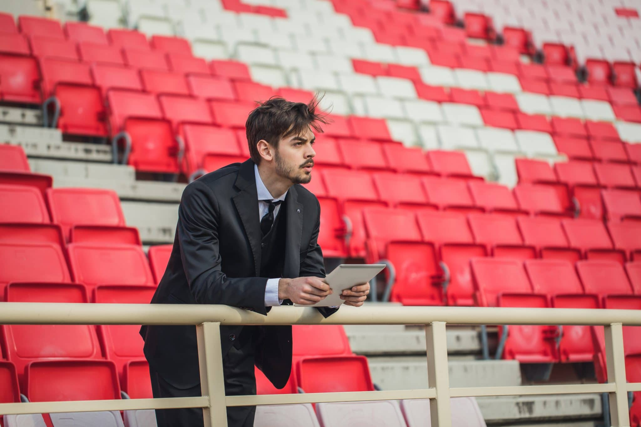 One man, young and handsome, soccer manager on the bleachers, using digital tablet.